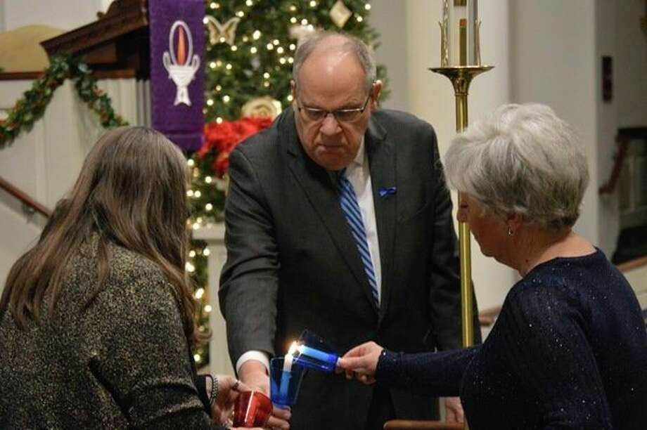 From left, Laura Currie, Reverend Wallace Mayton and Mary Fisher light candles to honor fallen police, firefighters and paramedics during the Project Blue Light ceremony at Memorial Presbyterian Church. (Mitchell Kukulka/Mitchell.Kukulka@mdn.net)