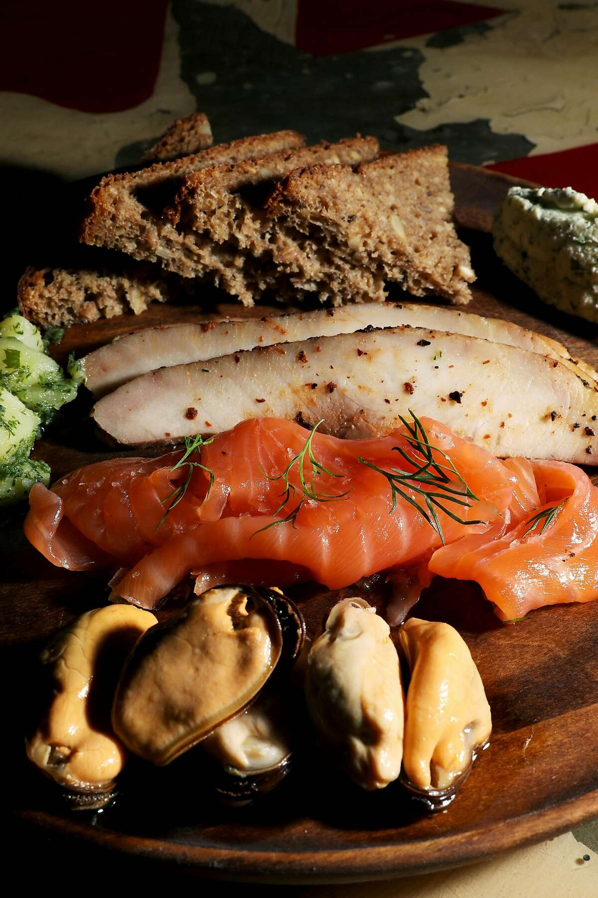 Smoked fish plate features smoked sturgeon, cured salmon, pickled mussels, farmer's cheese, German potato salad, and seeded rye at Dear Inga, located at 3560 18th St., in San Francisco, Calif., on Friday, December 6, 2019.