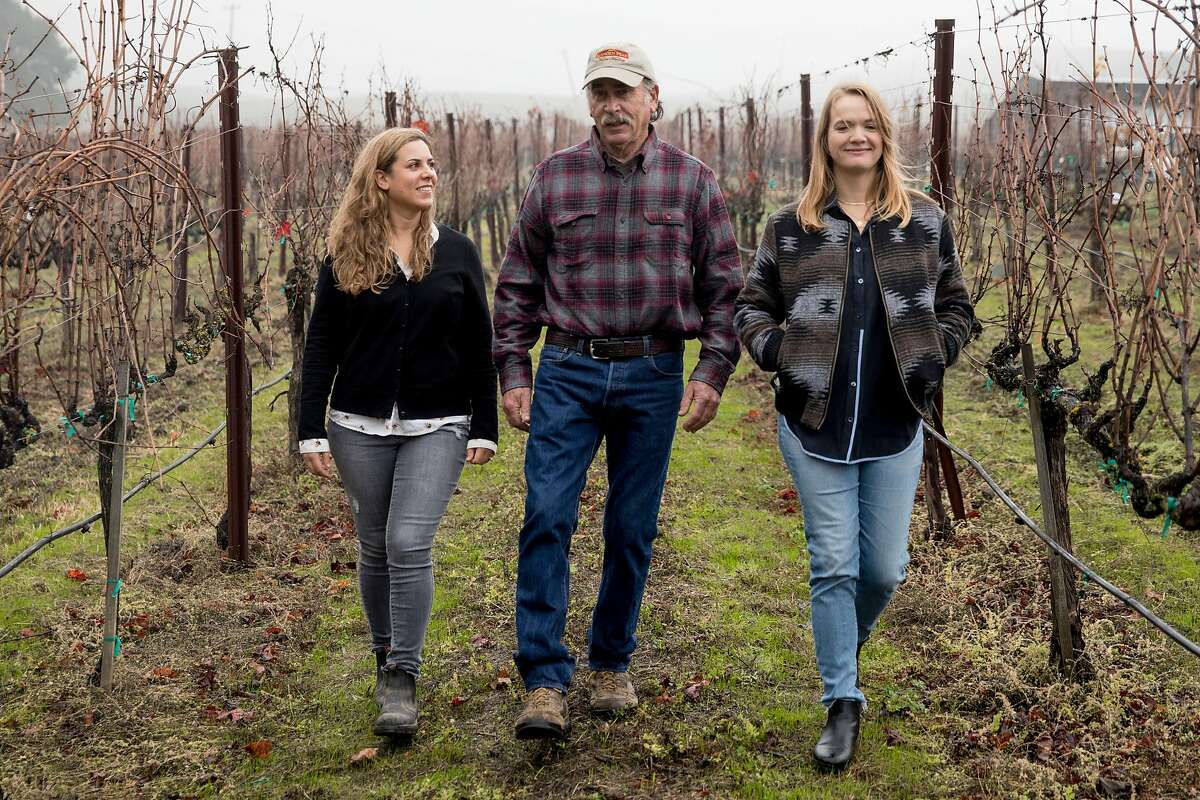 Elkhorn Peak Cellars owner Ken Nerlove (center) and his daughters and fellow Save the Family Farms members Hayley Hossfeld (right) and co-ownar Elise Nerlove chat while walking through their vineyard in Napa, Calif. Wednesday, Dec. 11, 2019.