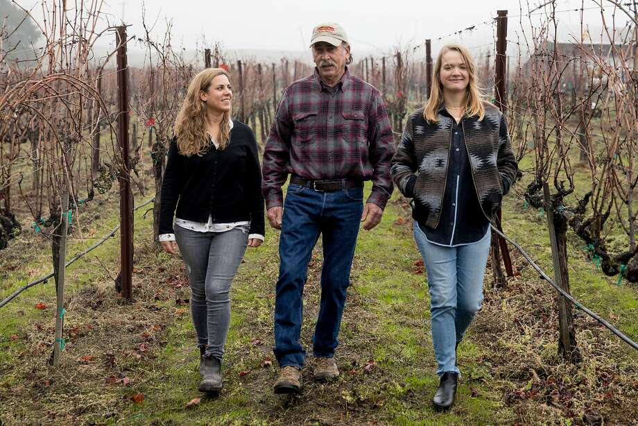 Elkhorn Peak Cellars owner Ken Nerlove (center) and his daughter Elise Nerlove Rutchick (left) walk through the vineyard with Hayley Hossfeld of Hossfeld Vineyards, another member of Save the Family Farms. Photo: Jessica Christian / The Chronicle