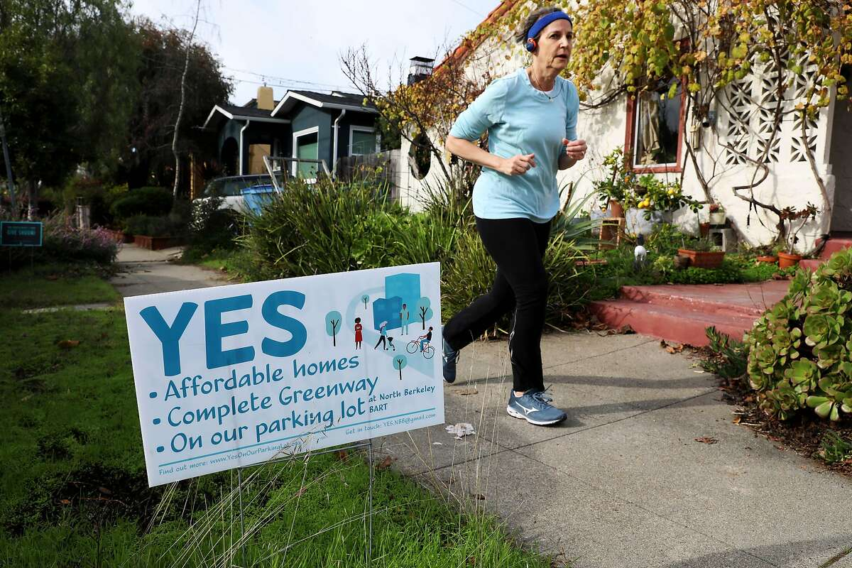 A jogger passes a yard sign on Virginia Street that favors affordable homes in North Berkeley, Calif., on Tuesday, December 17, 2019.