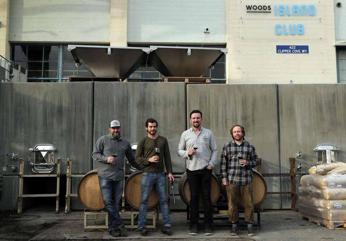 The crew at Wood's Island Club, l-r, Chris Scanlan, consulting winemaker, Kyle Jeffrey, assistant winemaker, Jim Woods, founder and CEO, and Kim Sturdavant, head brewer, in front of the concrete wine tanks on Treasure Island in San Francisco, Calif., on Tuesday, December 10, 2019. A new state law in California, takes effect Jan 1, that will allow wineries, breweries and distilleries to have overlapping licenses. Woods Beer Co. is now also making wine at its Treasure Island facility.