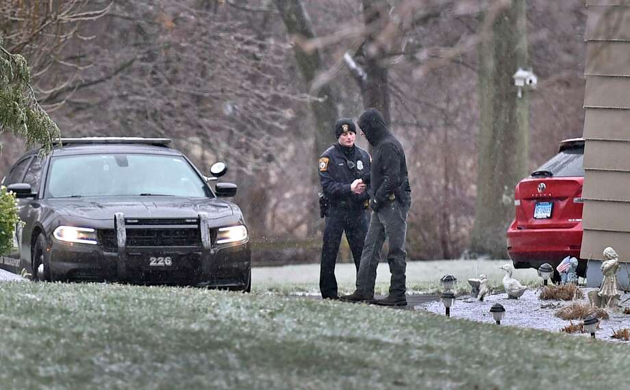 A Bridgeport police officer and detective at 20 Claudia Drive in Milford Tuesday, where a car, seen at right, was abandoned by suspects in a Bridgeport shooting. Photo: Peter Hvizdak / Hearst Connecticut Media / New Haven Register