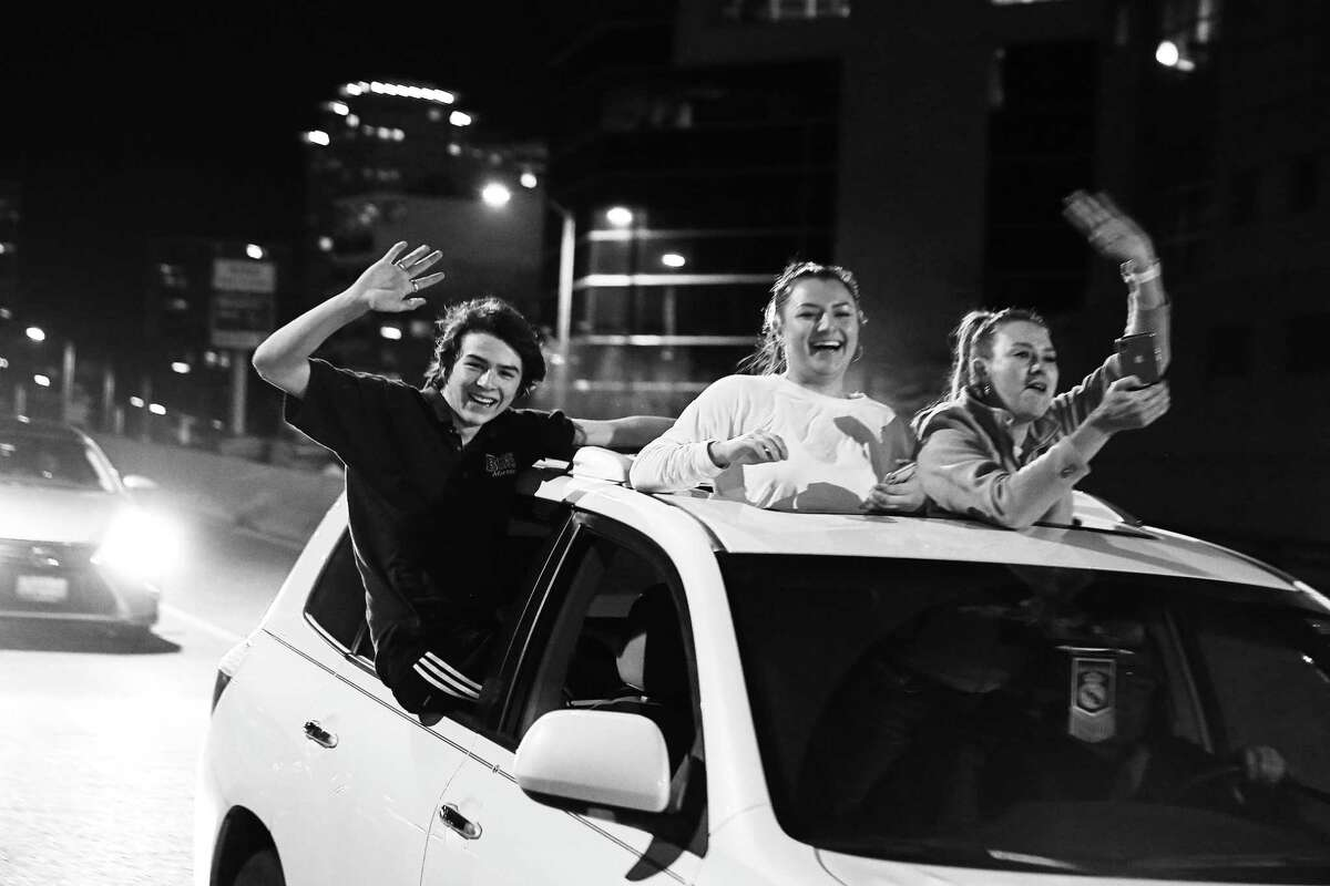 People wave from their cars as others walk around on the Alaskan Way Viaduct as it is closed for the final time before its demolition, Friday, Jan. 11, 2019. Hundreds continued to mob the viaduct, honking and yelling out car windows long past its scheduled 10 p.m. closure time. Some even drove around DOT trucks and barriers to get onto the road.