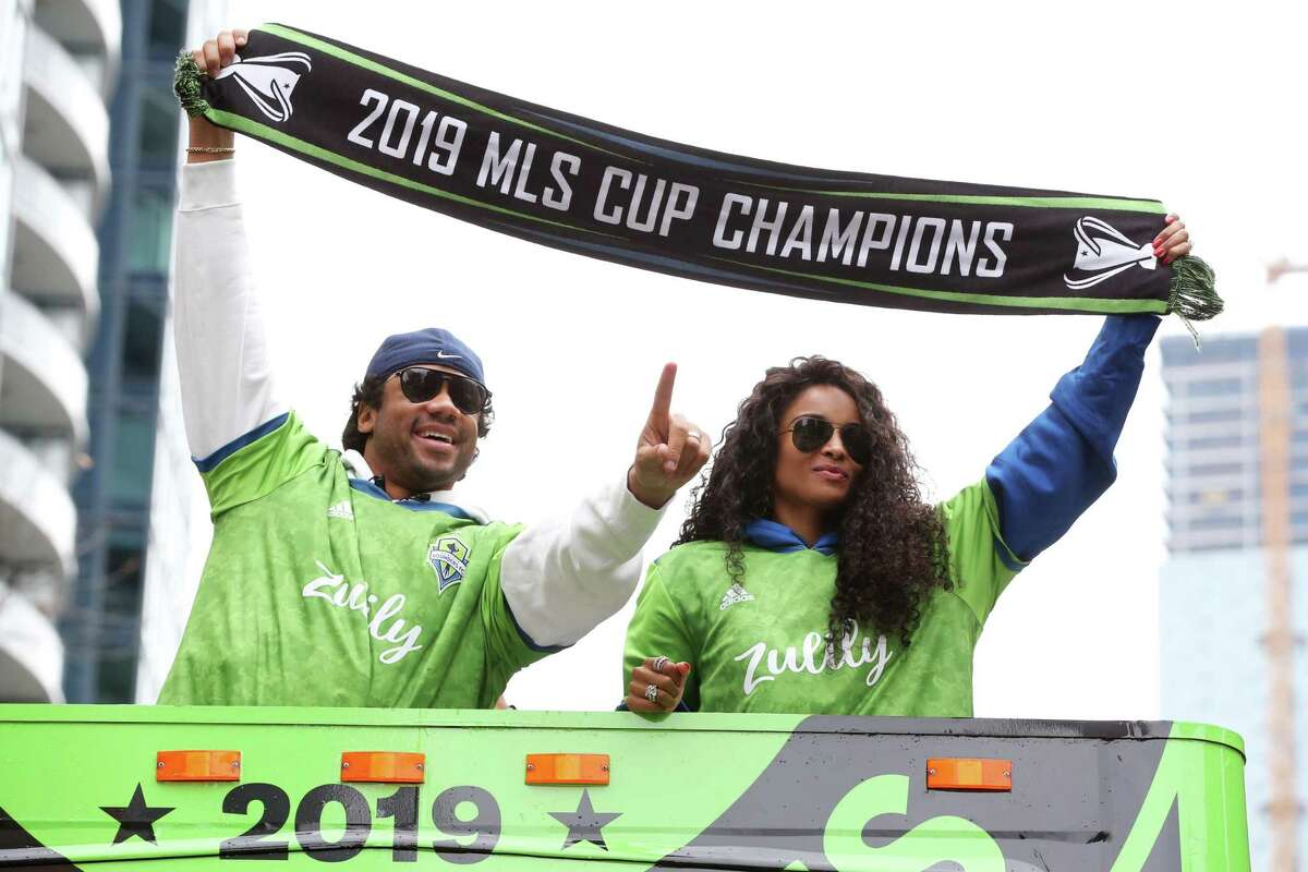 Sounders co-owners Russell Wilson and Ciara hold up a championship scarf as the City of Seattle celebrates the Sounders' MLS Cup Championship win with a parade from Westlake Park to Seattle Center and a rally, Tuesday, Nov. 12, 2019. The Sounders beat Toronto 3-1 to bring home their second MLS Cup in four years.
