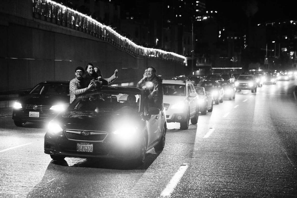 People wave and take video from their cars as others walk around on the Alaskan Way Viaduct as it is closed for the final time before its demolition, Friday, Jan. 11, 2019. Hundreds continued to mob the viaduct, honking and yelling out car windows long past its scheduled 10 p.m. closure time. Some even drove around DOT trucks and barriers to get onto the road.