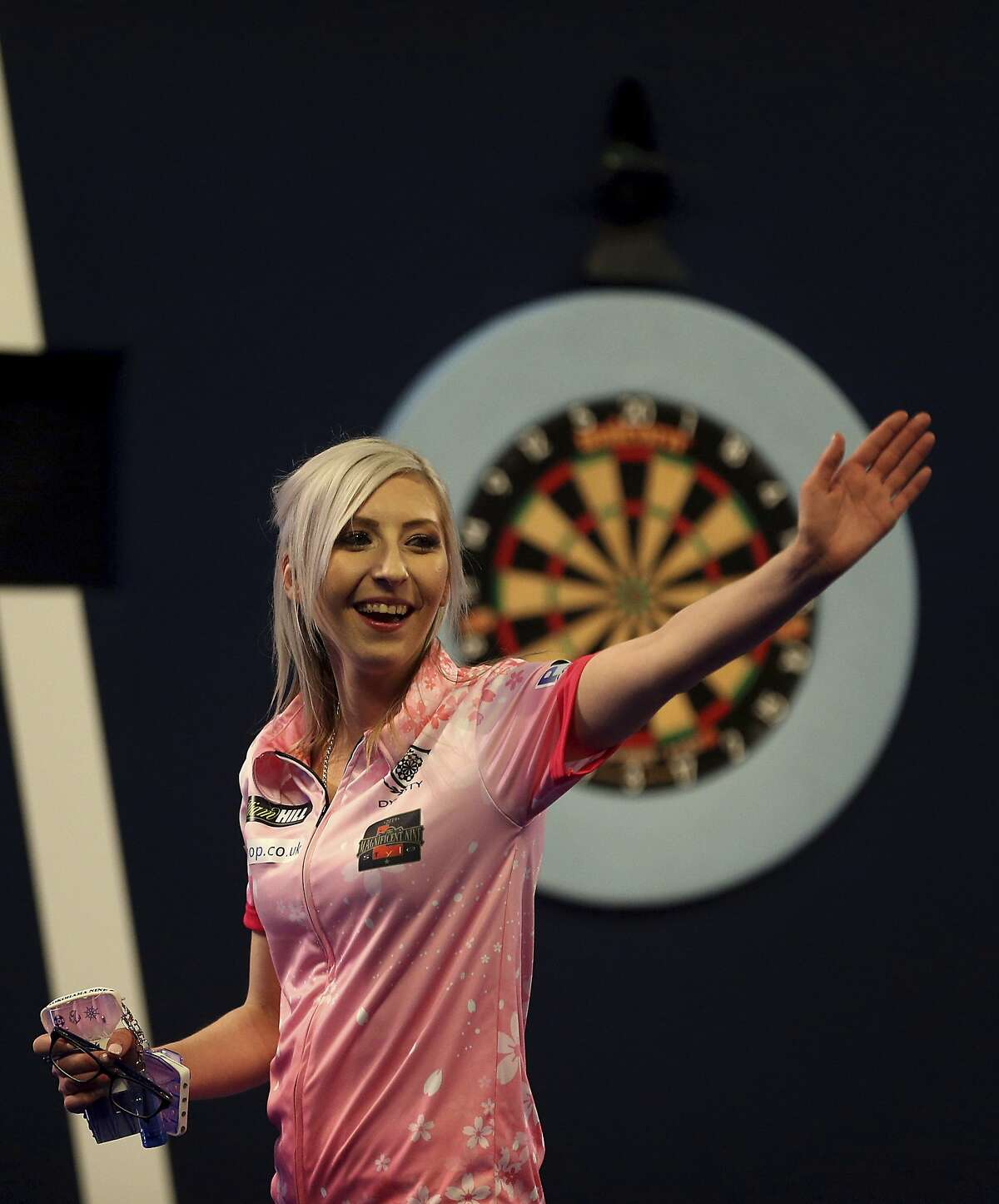 Fallon Sherrock celebrating after becoming the first women to win a game in the PDC Darts World Championship at Alexandra Palace, London, Tuesday Dec. 17, 2019. Sherrock become the first female player to beat a man at the PDC World Championship after she recovered from losing the opening set to beat Ted Evetts 3-2 in front of a raucous crowd at Alexandra Palace. (Steven Paston/PA via AP)