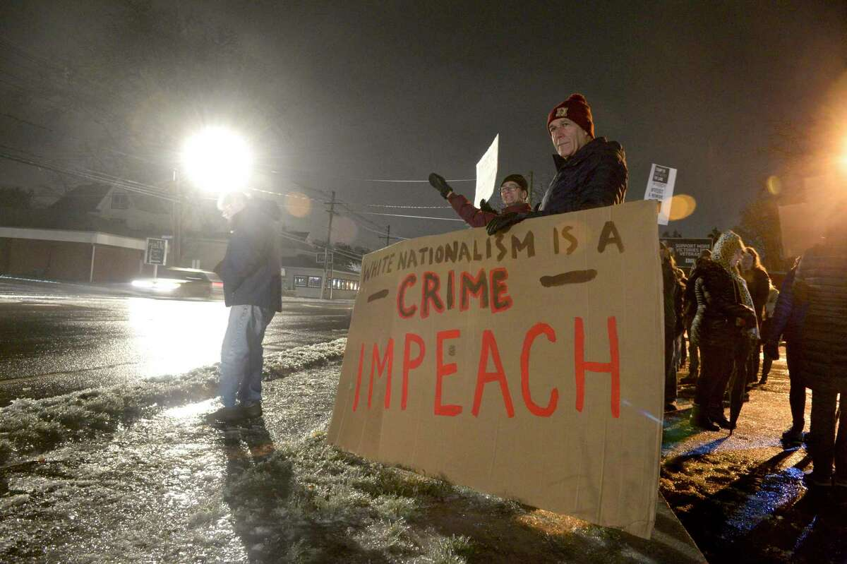 Ed Edelson, right, former First Selectman of Southbury, stands behind a sign as community members rally for the impeachment of President Trump at the corner of Greenwood Ave and Route 53 on Tuesday evening. December 17, 2019, in Bethel, Conn.
