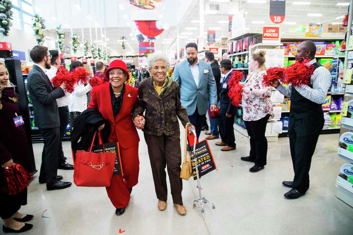 """Lillie Lockett, who is """"over 70"""" and her next door neighbor Eva Harvey, 90, hold hands as they walk in between two lines of HEB employees cheering for the members of the Third Ward community as they enter the new HEB store on MacGregor on Tuesday, Dec. 17, 2019, in Houston. Lockett has been a Third Ward resident for more than 25 years and Harvey has been a resident for more than 50 years."""
