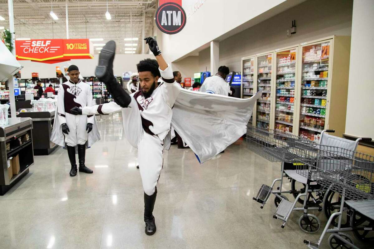 Joshua Stewart, 20, member of the Texas Southern University's marching band Ocean of Soul practices his moves in the new H-E-B MacGregor Market on Tuesday, Dec. 17, 2019, in Houston while waiting for the opening store reception.