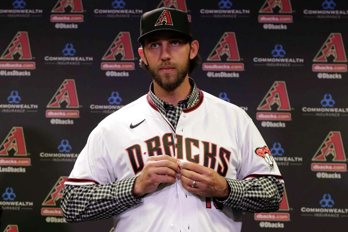 Newly acquired Arizona Diamondbacks pitcher Madison Bumgarner puts on his new jersey after being introduced during a team availability, Tuesday, Dec. 17, 2019, in Phoenix. (AP Photo/Matt York)