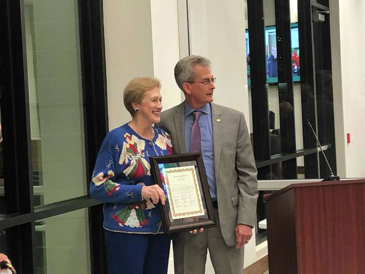 At a reception on Monday, Dec. 16, at Bellaire City Hall, City Manager Paul Hofmann presents outgoing Council Member Trisha Pollard with a framed letter from the city staff for her four years a council member.