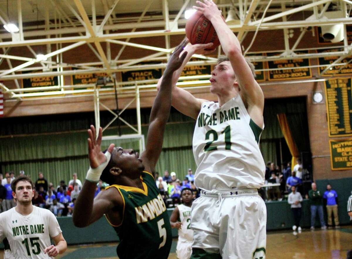 Notre Dame-West Haven's Zach Laput (21) looks to score over Hamden's Jayvon Chapman during a game earlier this month.