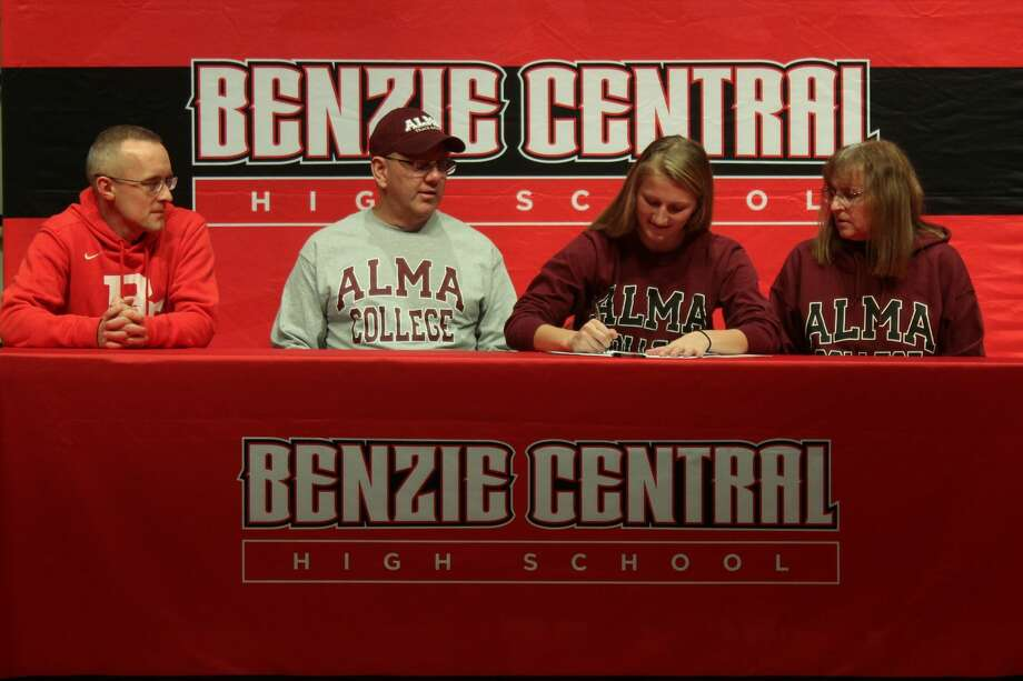 Andrea Taghon signs her letter of intent to run track and cross country for Alma College, supported by her father Dennis Taghon (left), her mother Elaine Taghon (right) and her coach Asa Kelly (far left). Photo: Robert Myers