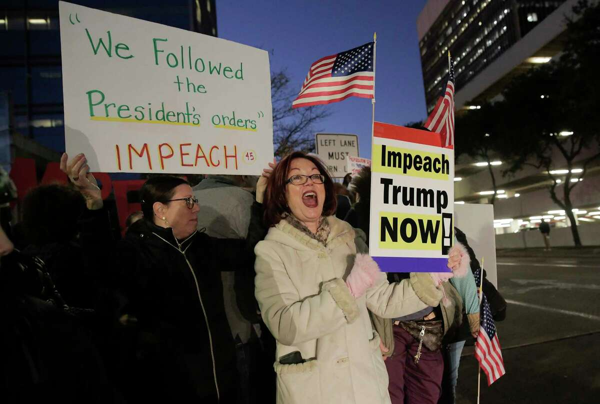 Gretchen Lindquist of Houston holds a sign in support of impeaching Trump with other Houstonians outside the office of U.S. Sen. Ted Cruz as part of a national protest in support of impeachment on Tuesday, Dec. 17, 2019 in Houston.