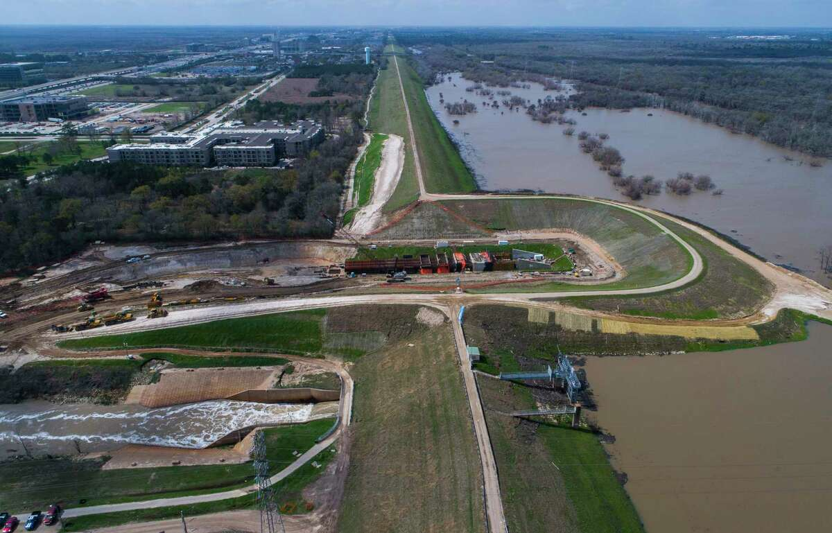 Water flows out of the Addicks Reservoir down the main spillway near N. Eldridge Pkwy., Wednesday, Feb. 28, 2018, in Houston. A coffer dam is in place where the Army Corps of Engineers is building a new spillway. ( Mark Mulligan / Houston Chronicle )