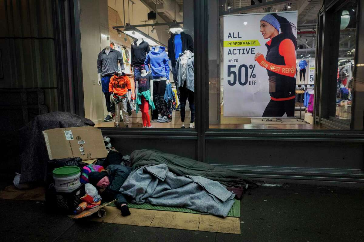 FILE - In this Jan. 11, 2017, file photo, a homeless person sleeps under a blanket outside an Old Navy store window display in New York. Mayor Bill de Blasio released a plan Tuesday, Dec. 17, 2019, to get nearly all of the estimated 3,600 people who are living on New York City streets and (AP Photo/Mark Lennihan, File)
