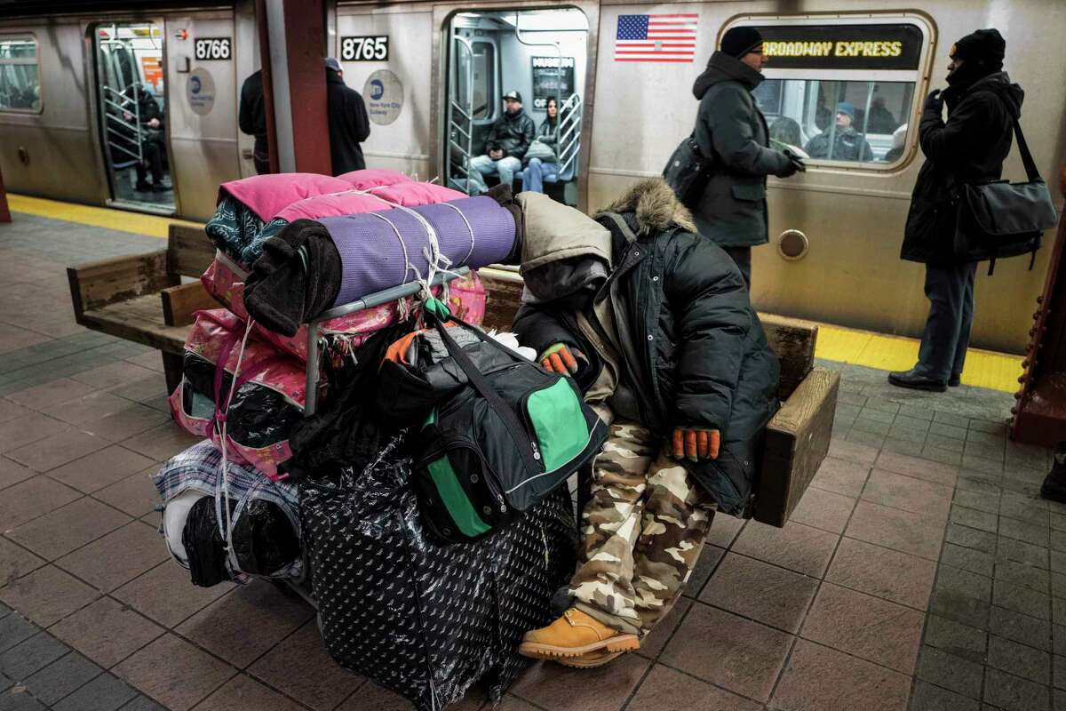 FILE - In this Jan. 10, 2017, file photo, a homeless man sleeps with his belongings on a subway platform bench in New York. Mayor Bill de Blasio released a plan Tuesday, Dec. 17, 2019, to get nearly all of the estimated 3,600 people who are living on New York City streets and (AP Photo/Mark Lennihan, File)
