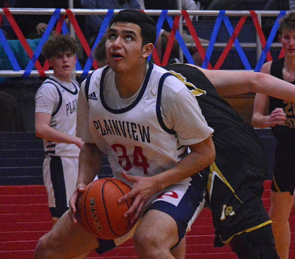 Plainview's Jesus Quiroga gets around an Amarillo defender for a shot near the basket during their District 3-5A boys basketball game on Tuesday night in the Dog House. Looking on is Plainview's Austin Hauk.