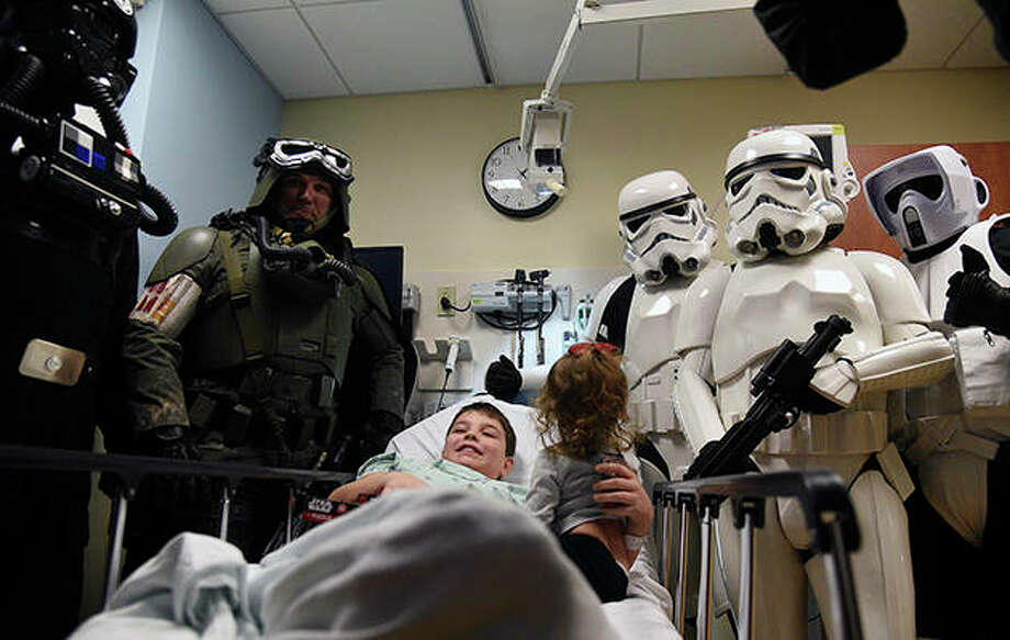 """Patient Brandon Callison, 10, of Warrenville and his sister, Quinlan, 1, get a visit from """"Star Wars"""" characters at Northwestern Medicine Central DuPage Hospital in Winfield. The visitors were members of the Midwest Garrison, which is the Illinois chapter of The 501st Legion, a """"Star Wars"""" Imperial costuming club. The group is dedicated to the movie-quality costumes of the villains of the """"Star Wars"""" universe. Brandon was in the hospital after recovering from a trampoline injury. Photo: Rick West 