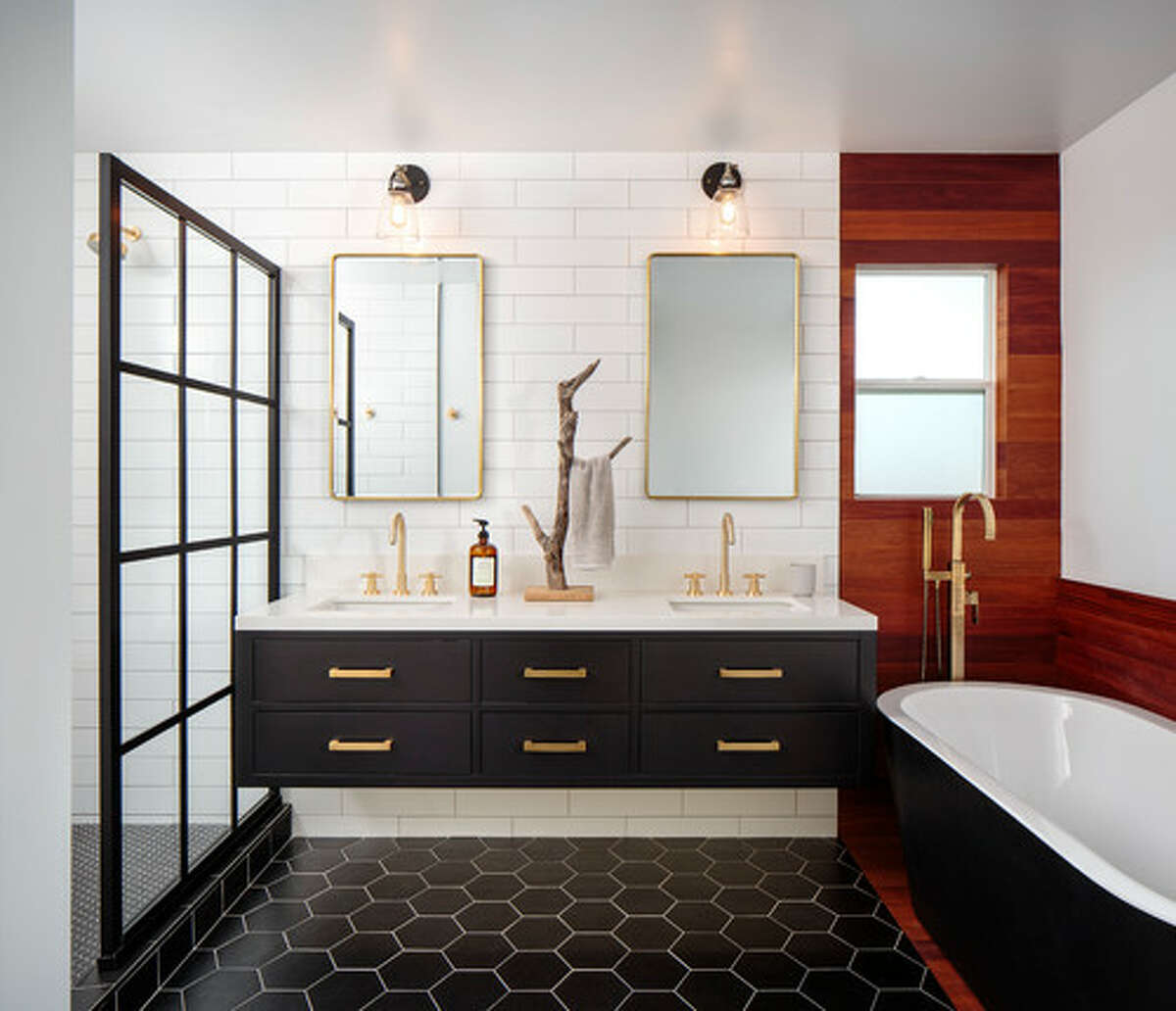 """2. Black is back Some may say this is the pendulum swinging away from all-white interiors, but many of our experts predict that black furnishings will be bigger than ever in 2020. Brett Elron, owner and lead interior designer at BarterDesign.co in New York, says we will see black on larger design elements like accent walls, sofas, and cabinets. """"And if you pair up your dark doors with great hardware, you really add some character to your home,"""" he says. Gray-Plaisted agrees, saying that black cabinetry is the new alternative to white. """"If black cabinetry is too much for you in a kitchen, consider the lowers to be done in black and the uppers done in wood,"""" she recommends. Anne R. Kokoskie of Styled by ARK says that she expects to see the rise of black tubs and bold, dark colors on doors."""