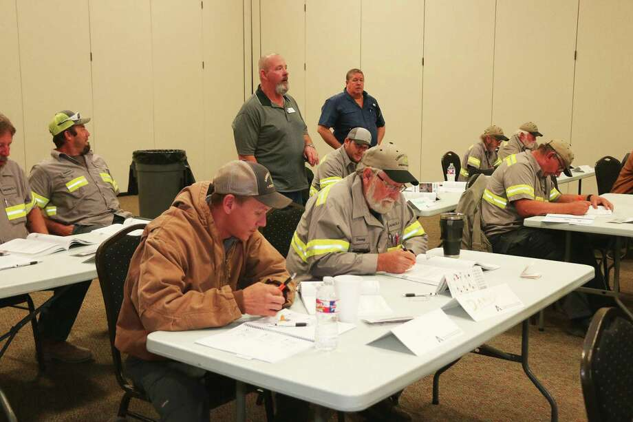 Jared Graves and Danny Earp look over their notes while Instructor Glen Cardiff and Pct. 4 Commissioner Leon Wilson look on. The training was most of the day on Thursday. Photo: David Taylor / Staff Photo