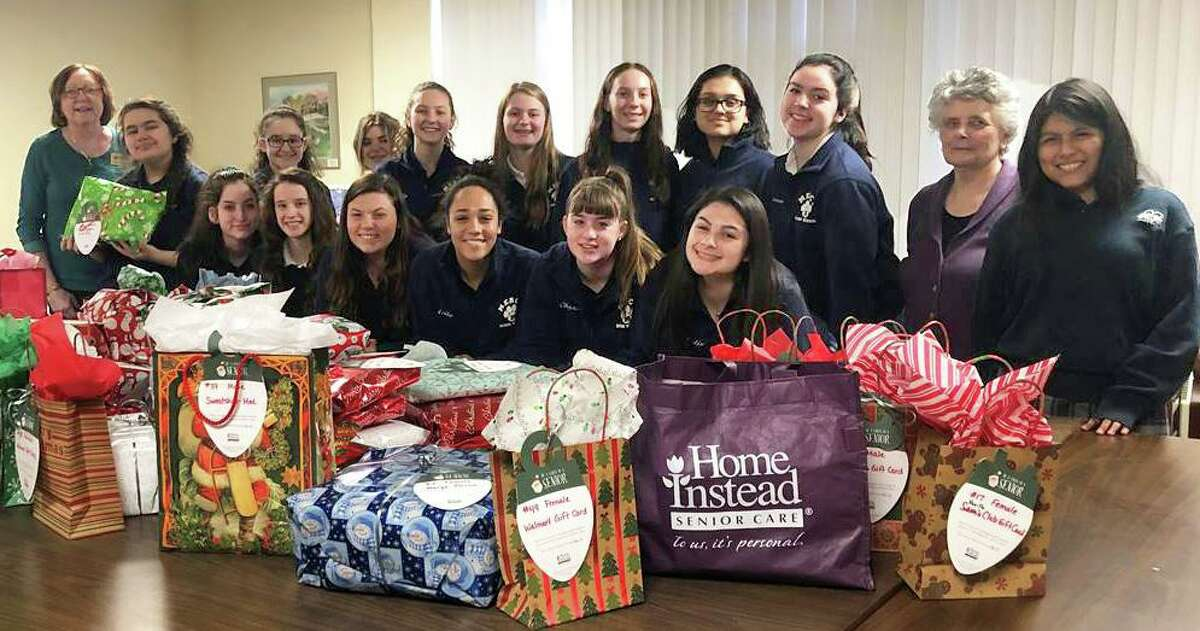Home Instead Senior Care of Middletown brought gift donations to Mercy High School Monday for a wrapping party organized by Ann Derbacher, campus minister and Theology Department chairwoman. Twenty-two student volunteers, shown, wrapped the presents and signed Christmas cards. At far left is Tracy Newmark, Home Instead home care consultant; and, at far right, Derbacher.