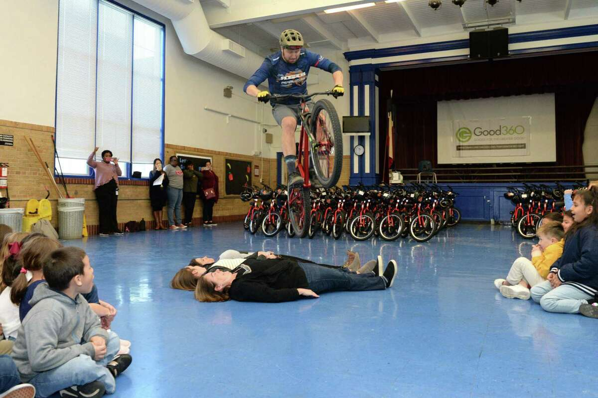 Pro Mountain Biker Jeff Lenosky performs tricks for first grade students at Field Elementary School before they are each given a new bicycle and helmet courtesy of Can'd Aid and Good360 on Tuesday, December 17, 2019 in Houston, TX.