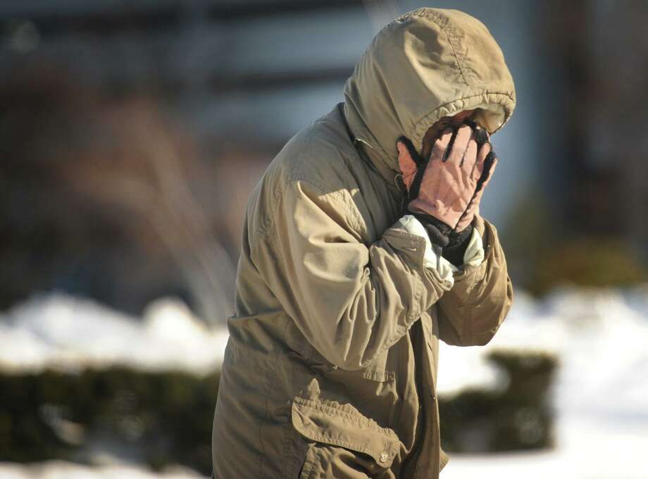 A man covers his face from the cold, biting wind on Fairfield Avenue in Bridgeport, Conn. Photo: Brian A. Pounds / Brian A. Pounds / Connecticut Post