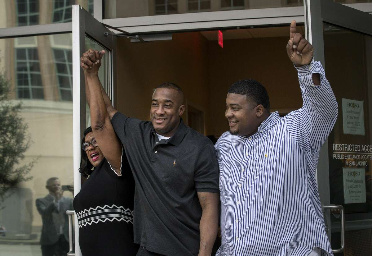 Lydell Grant, center, his mother Donna Poe, left, and brother Alonzo Poe celebrate Grant's release on bond on Tuesday, Nov. 26, 2019, in Houston. Earlier in the day, Grant was ordered released on bond after prosecutors and defense attorneys with the Innocence Project of Texas agreed that Grant should be released while the case is investigated further in light of new DNA evidence. Grant was convicted of capital murder in the 2010 stabbing death of Aaron Scheerhoorn outside of a Montrose bar, and he had spent seven years behind bars.