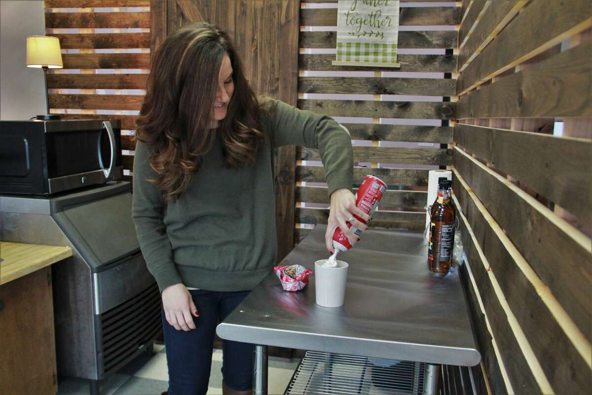 The Corner Cup owner Julia Raglin tops a hot cup of cocoa with whipped cream.