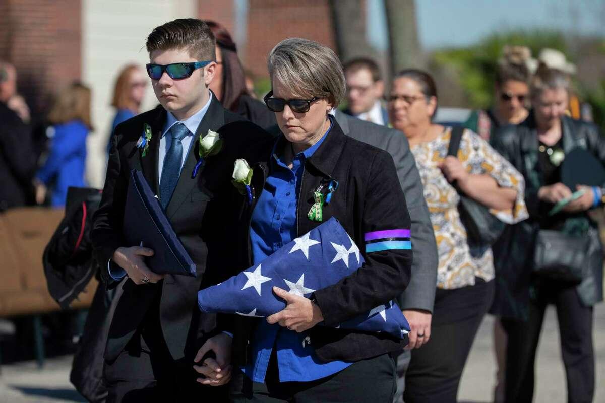 Tracey Sullivan, center, and her son Kaden Senter follow the casket of Senter's mother Nassau Bay Police Department Sgt. Kaila Sullivan on Wednesday, Dec. 18, 2019, in Houston.