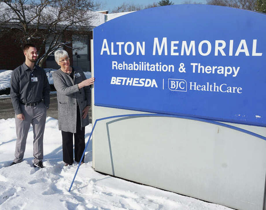 Daniel Vogel, administrator, and Hazel Morgan, referral coordinator, watch as the new Alton Memorial Rehabilitation & Therapy sign is installed outside the former Eunice Smith Home on Tuesday, Dec. 18.