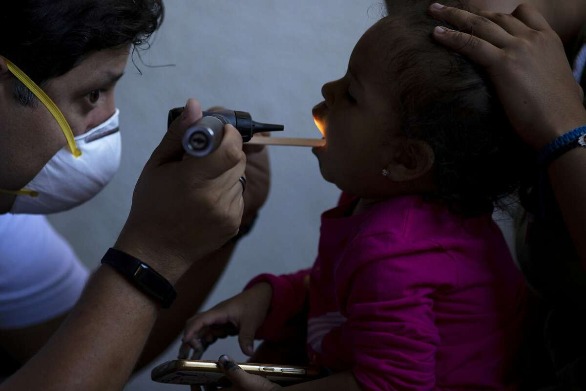 In this Oct. 26, 2019, photo, dentist Demetrio Cardenas, left, checks inside the mouth of a patient in a shelter for migrants in Tijuana, Mexico. The health crisis spans both sides of the border. In the past year, at least three children, detained by U.S. Border Patrol agents, have died from the flu while being held. They include a 16-year-old boy who was seen on security footage writhing in agony on the floor in a U.S. Border Patrol holding cell. (AP Photo/Gregory Bull)