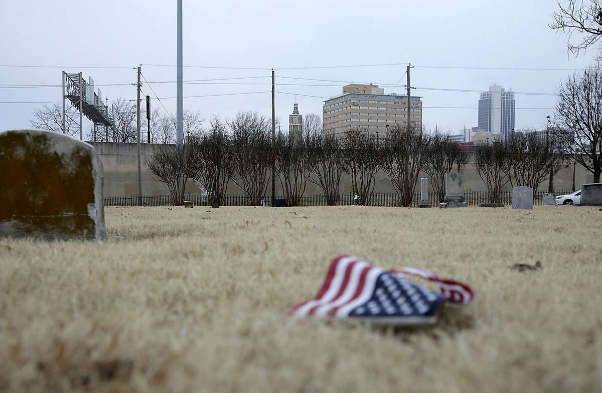 An American flag lies on the ground in front of an area of Oaklawn Cemetery. Tuesday, Dec. 17, 2019. in Tulsa, Okla., where a 25-by-30 foot apparent pit, consistent with a common grave, was located during initial scanning for unmarked graves related to the 1921 Tulsa Race Massacre. (Mike Simons/Tulsa World via AP)