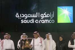 FILE - In Dec. 11, 2019, file photo Saudi Arabia's state-owned oil company Armco and stock market officials celebrate during the official ceremony marking the debut of Aramco's initial public offering (IPO) on the Riyadh's stock market, in Riyadh, Saudi Arabia. Saudi Aramco became the world's most valuable public company this year with a highly anticipated stock offering in December. (AP Photo/Amr Nabil, File)
