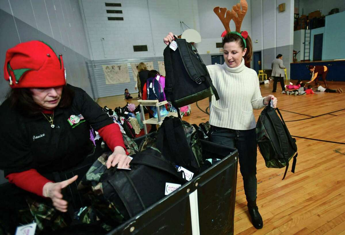 Volunteers with Filling in Blanks, including Janice Mariani of Angela's Specialties Fine Foods and Karen Newman help deliver over 200 holiday backpacks to Maritime Odyssey Preschool students Wednesday, December 18, 2019, at Nathnaiel ely School in Norwalk, Conn. The new backpacks were filled with special gifts for the holidays, including a book, a toy, pancake mix with syrup, a hat, gloves, socks, a toothbrush, and toothpaste. Filling in the blanks delivers over 500 take home meals to underprivileged children in Norwalk Public School every week.