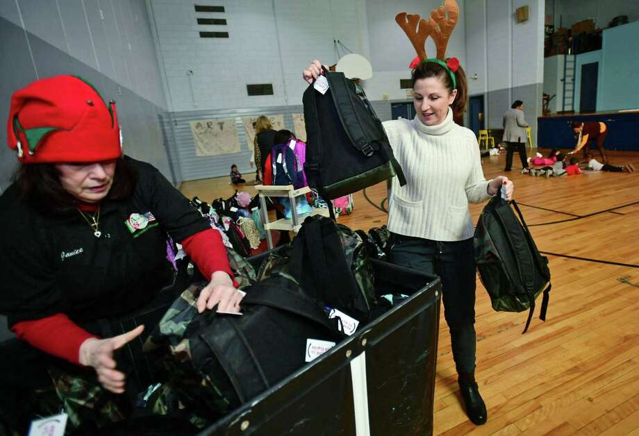 Volunteers with Filling in Blanks, including Janice Mariani of Angela's Specialties Fine Foods and Karen Newman help deliver over 200 holiday backpacks to Maritime Odyssey Preschool students Wednesday, December 18, 2019, at Nathnaiel ely School in Norwalk, Conn. The new backpacks were filled with special gifts for the holidays, including a book, a toy, pancake mix with syrup, a hat, gloves, socks, a toothbrush, and toothpaste. Filling in the blanks delivers over 500 take home meals to underprivileged children in Norwalk Public School every week. Photo: Erik Trautmann / Hearst Connecticut Media / Norwalk Hour