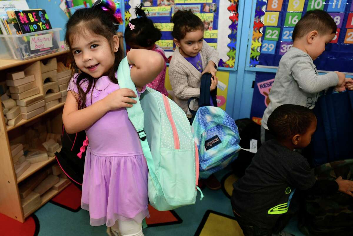 Preschooler Michelle Betancourt picks out her backpack after volunteers with Filling in Blanks delivered over 200 holiday backpacks to Maritime Odyssey Preschool students Wednesday, December 18, 2019, at Nathnaiel ely School in Norwalk, Conn. The new backpacks were filled with special gifts for the holidays, including a book, a toy, pancake mix with syrup, a hat, gloves, socks, a toothbrush, and toothpaste. Filling in the blanks delivers over 500 take home meals to underprivileged children in Norwalk Public School every week.