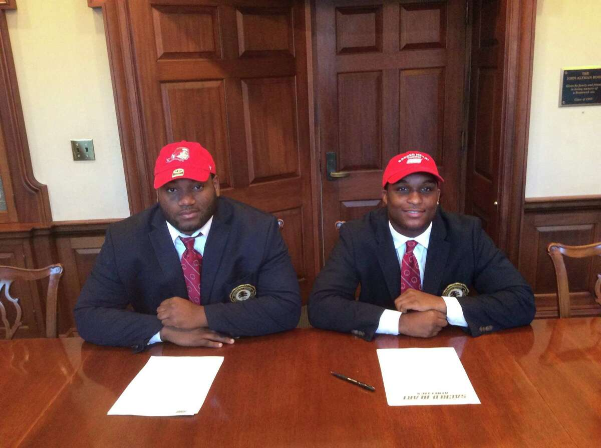 Howard Powell, left, and Jalen Madison each signed National Letters of Intent to play football at Sacred Heart University.