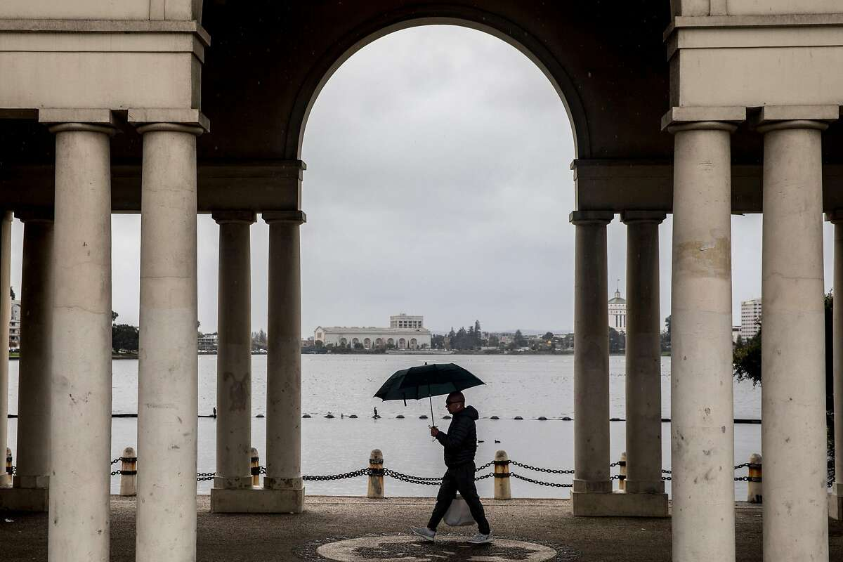 A man (no name given) walks with an umbrella around Lake Merritt during a rainy morning in Oakland, Calif. Wednesday, December 18, 2019.