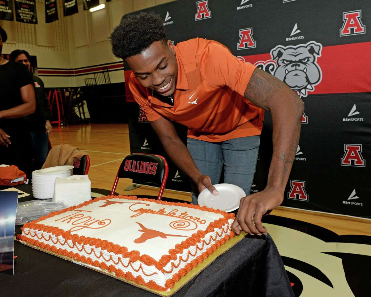 Troy Omeire of Ft. Bend Austin High School cuts a cake after signing a commitment to play for the University of Texas on National Signing Day, December 18, 2019 in Sugar Land, TX.