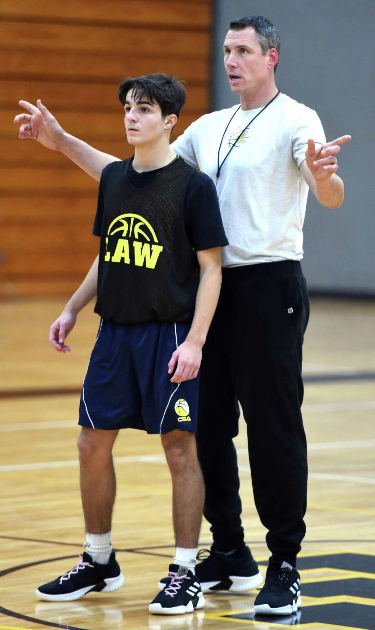 Law coach Jamie Anderson, right, goes over positioning with Jake Faller during practice in Milford on Friday.