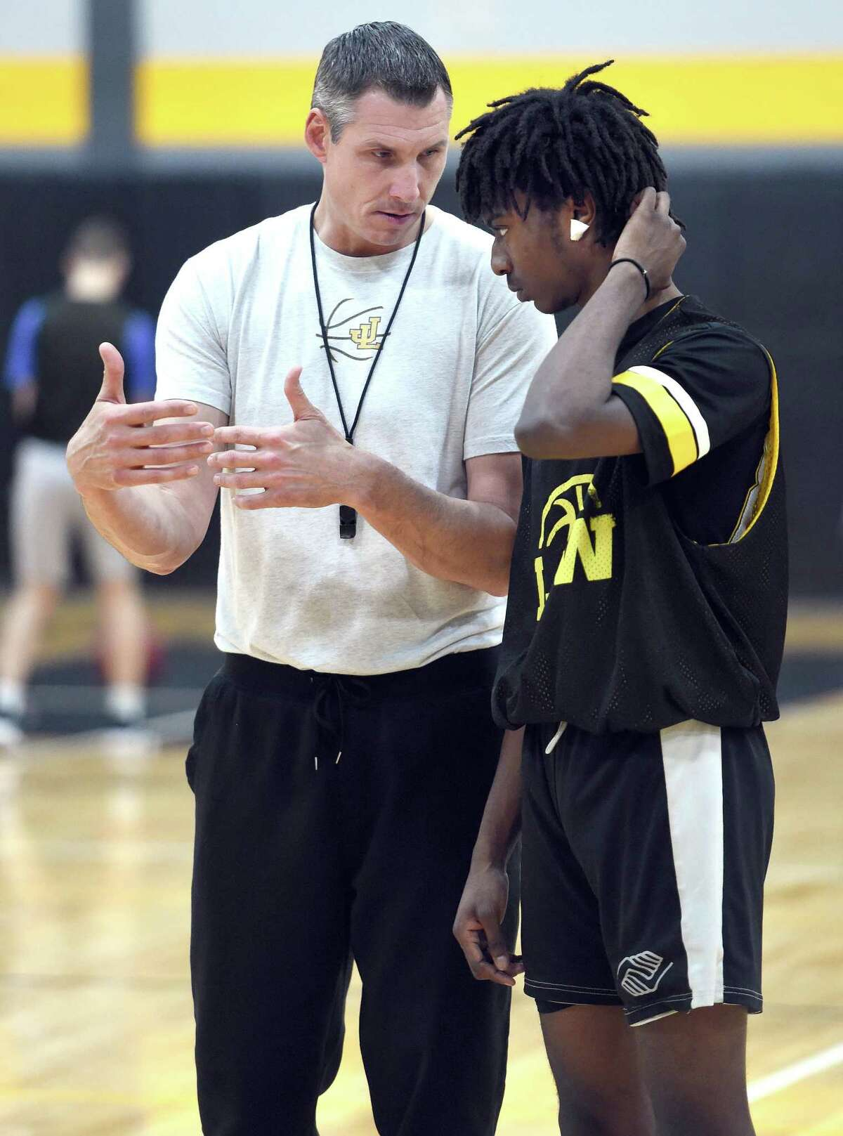 Law coach Jamie Anderson speaks with Diontae Eady during practice in Milford on Friday.
