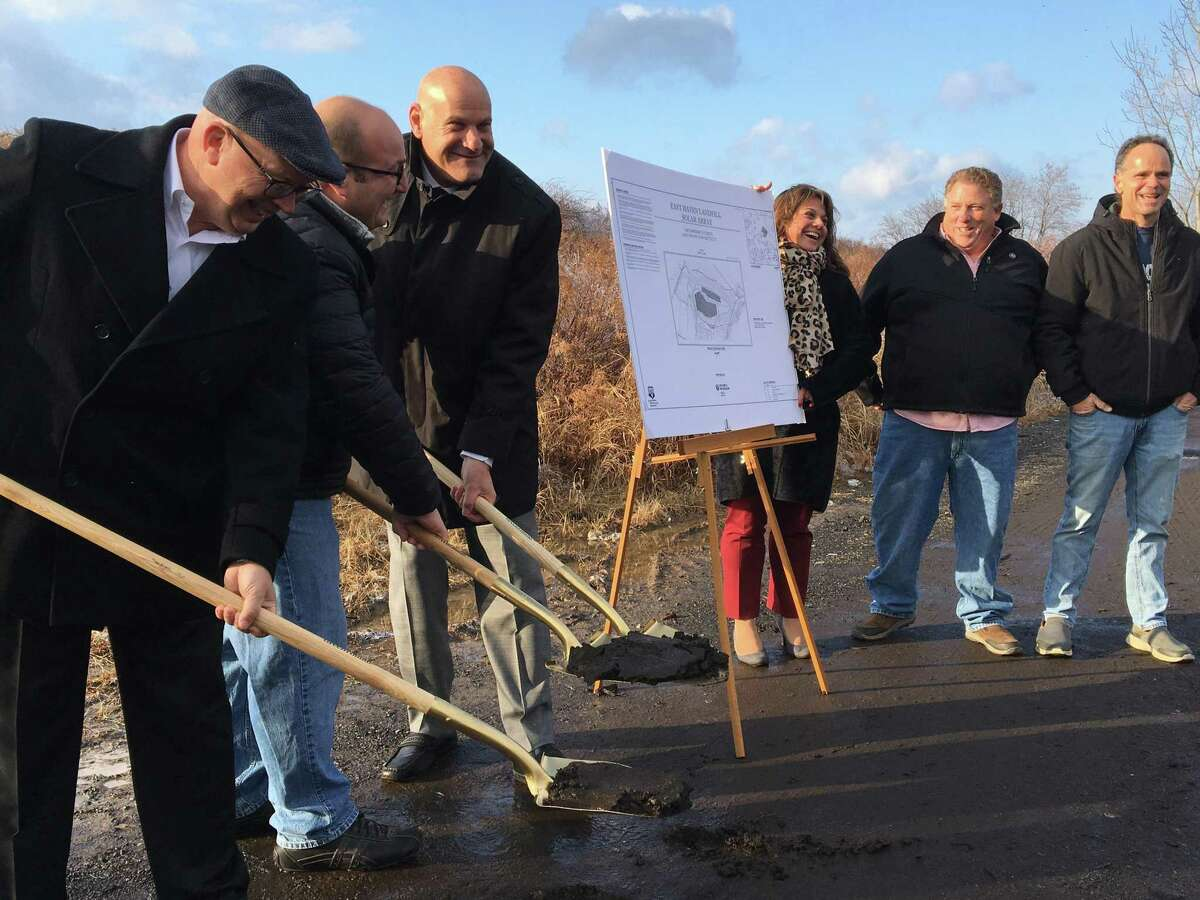 East Haven Mayor Joe Carfora, third from left, Town Council Chairman Joe Deko, D-2, second from left, and Greenskies Senior Vice President for Development Ron Wedeking break ground for Greenskies' new 1.3-megawatt solar farm atop the closed East Haven Landfill off Commerce Street Wednesday.