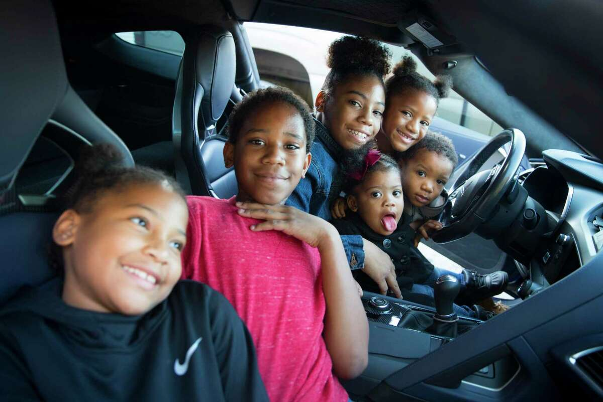 The children of Timeka Gray pose in a blue Corvette during the God's Garage Christmas party in Conroe.