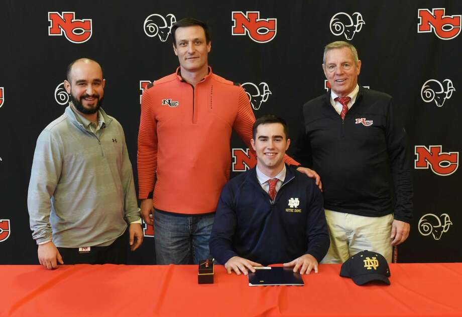New Canaan senior Drew Pyne with Ram coaches, from left, AJ Albano, Chris Silvestri and Lou Marinelli during the first day of the early signing period for football on Wednesday, Dec. 18, 2019, at NCHS. Pyne signed his National Letter of Intent to play for Notre Dame. Photo: Dave Stewart / Hearst Connecticut Media / Hearst Connecticut Media