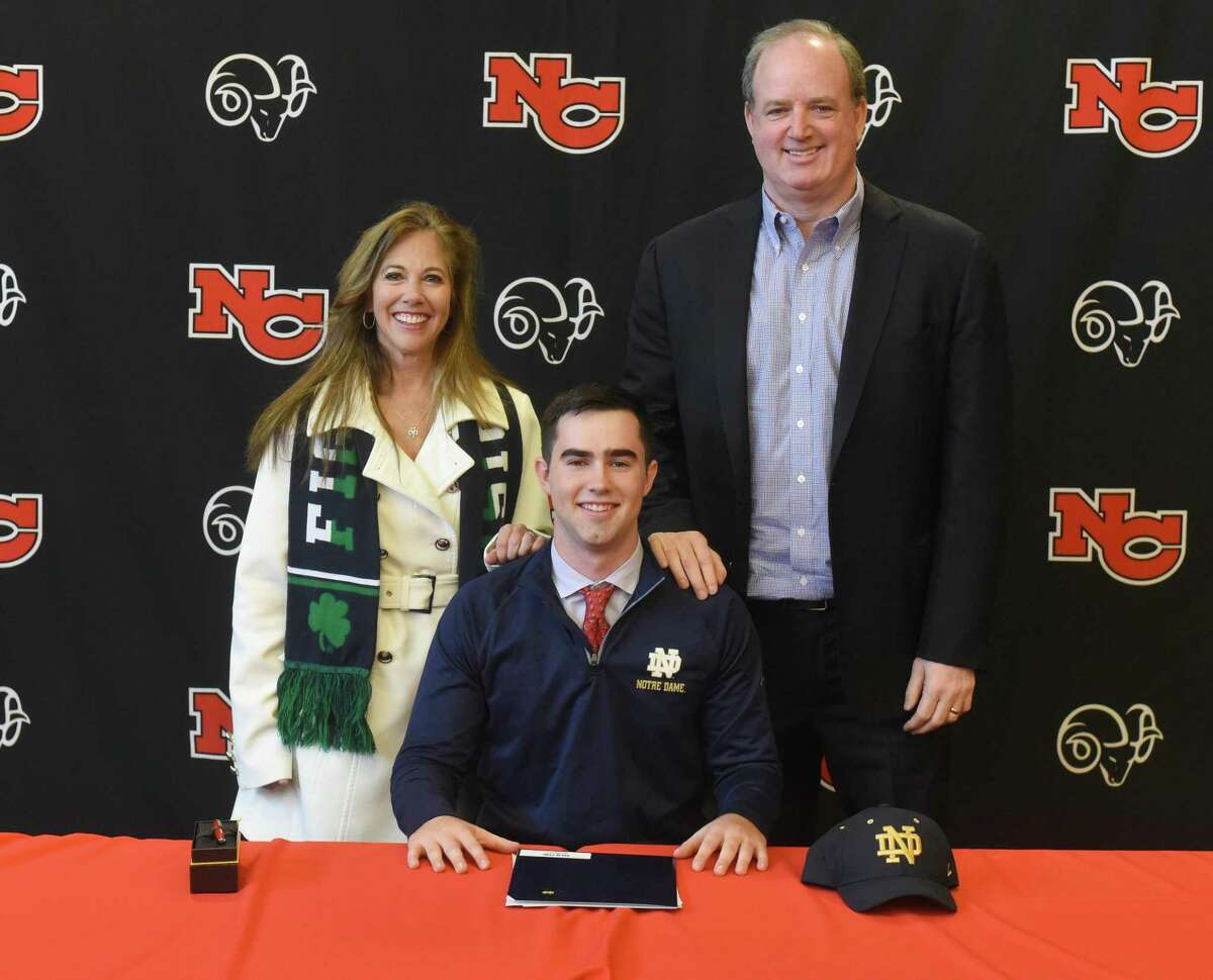 New Canaan senior Drew Pyne with his parents, Helene and George, during the first day of the early signing period for football on Wednesday, Dec. 18, 2019, at NCHS. Pyne signed his National Letter of Intent to play for Notre Dame.