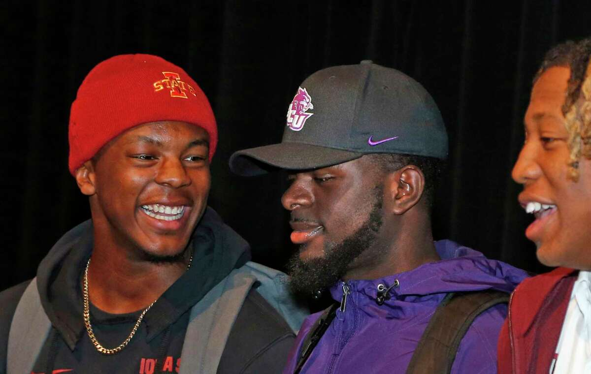 At Steele football signing day ceremony Daniel Jackson(Iowa State) smiles at Damion Hart(Abilene Christian) while having group photos taken on Wednesday, December, 18, 2019. On extreme right is Jaylon Jones(Texas A&M).
