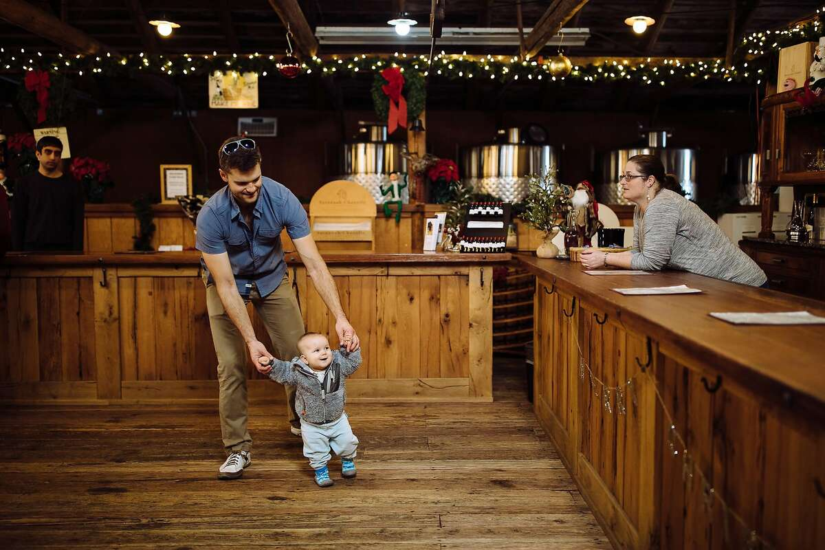Tim Ruckh helps his ten-month-old daughter, Evelyn Ruckh, walk at Savannah-Chanelle Winery's tasting room in Saratoga, Calif. Sunday, December 3, 2017.